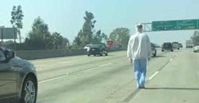 Hombre camina en la carretera con la cara vendada y un cuchillo en la mano